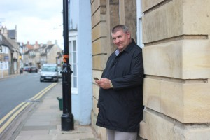 Most people going down West Street will have caught sight of Mark Bray (49) taking a break on West Street. Mark was a farmer in Lincolnshire for 25 years. When he met his partner Paul, in Peterborough in 2007, he moved in with him in Oundle, where Paul (70) used to run a fruit and vegetable shop at their home on West Street. In 2013 Paul suffered a debilitating stroke, and Mark is now his full time carer.